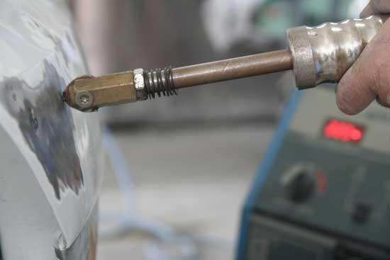 Многие мастера предпочитают выравнивать вмятины с лицевой стороны с помощью обратного молотка.